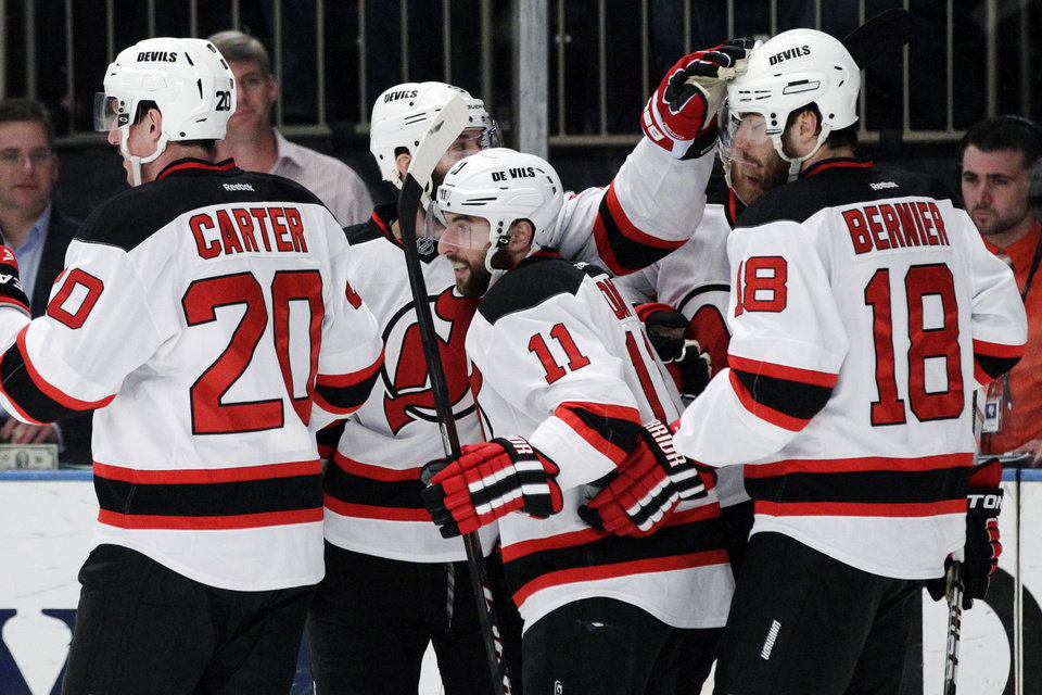 Photo -   New Jersey Devils' Stephen Gionta, center, celebrates with Ryan Carter, left, and Steve Bernier, right, after scoring against the New York Rangers during the first period of Game 5 of an NHL hockey Stanley Cup Eastern Conference final playoff series Wednesday, May 23, 2012, in New York. (AP Photo/Frank Franklin II)