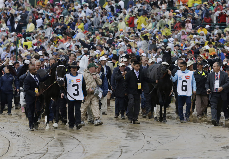 Grooms walk Derby horses Revolutionary (3) and Mylute (6) to the paddock area before the start of the 139th Kentucky Derby at Churchill Downs Saturday, May 4, 2013, in Louisville, Ky. (AP Photo/J. David Ake)