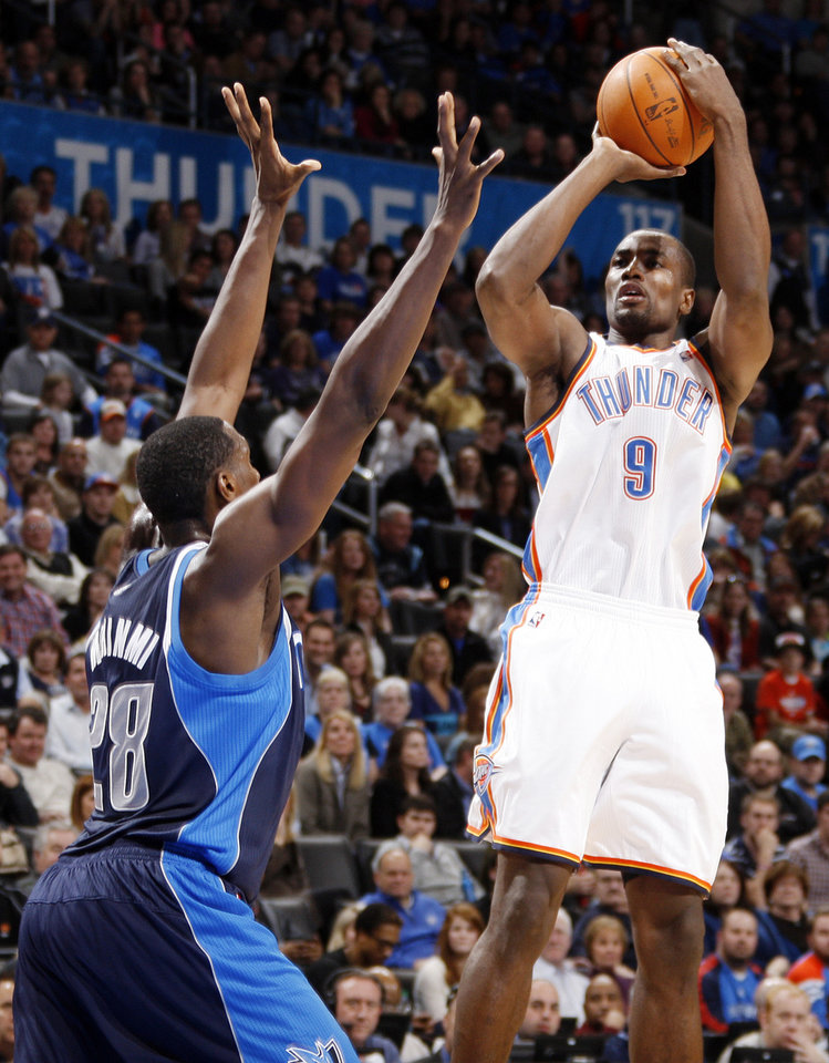 Oklahoma City's Serge Ibaka (9) takes a shot over Ian Mahinmi (28) of Dallas in the second half of an NBA basketball game between the Oklahoma City Thunder and the Dallas Mavericks at Chesapeake Energy Arena in Oklahoma City, Thursday, Dec. 29, 2011. Oklahoma City won, 104-102. Photo by Nate Billings, The Oklahoman