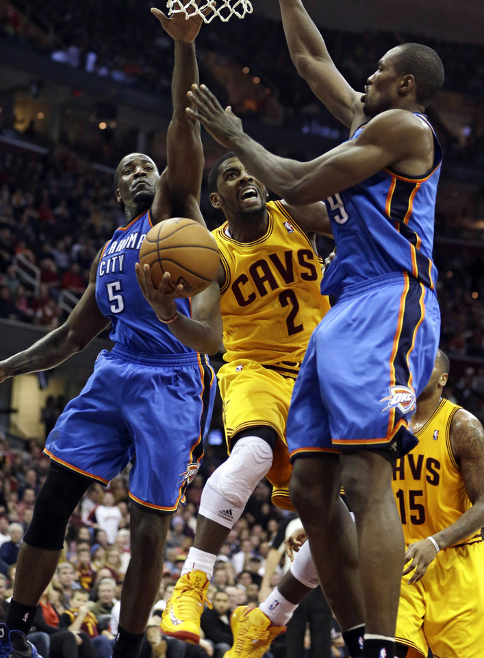 Cleveland Cavaliers\' Kyrie Irving (2) shoots to the basket against Oklahoma City Thunder\'s Kendrick Perkins (5) and Serge Ibaka (9), from the Republic of Congo, during the fourth quarter of an NBA basketball game on Saturday, Feb. 2, 2013, in Cleveland. The Cavaliers won 115-110. (AP Photo/Tony Dejak) ORG XMIT: OHTD109