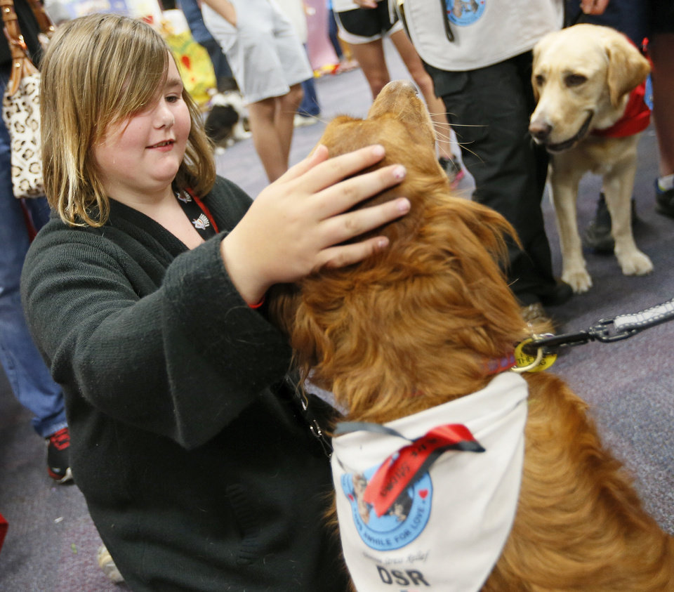 Photo - Third-grader Kayla Holt, 10, pets Calie, a therapy dog from Oklahoma City with Therapy Dogs International, during a meet and greet with teachers and students from Plaza Towers Elementary at Eastlake Elementary School in Oklahoma City, Thursday, May 23, 2013. Seven Plaza Towers students died when a tornado destroyed the school in Moore, Okla., on Monday. Holt was out of school on Monday to help her grandmother from Shawnee whose home was destroyed by a tornado on Sunday. She and her parents made it into an interior closet at their home in Moore just as the tornado destroyed the house. Photo by Nate Billings, The Oklahoman