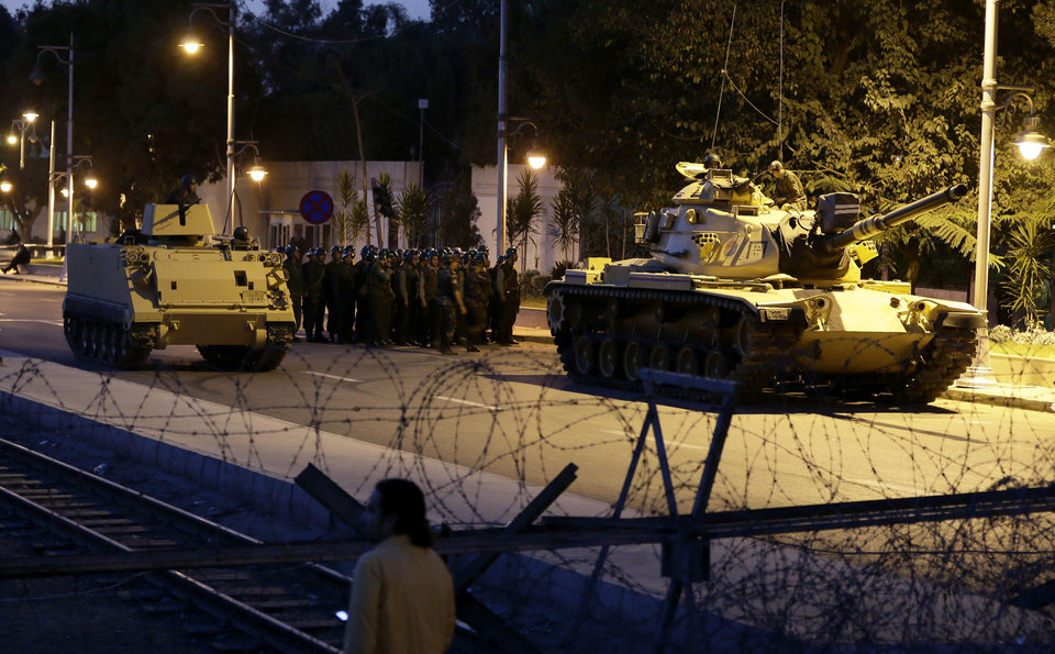 Photo - An Egyptian Army tank deploys outside the presidential palace, in Cairo, Egypt, Thursday, Dec. 6, 2012. The Egyptian army sealed off the presidential palace with barbed wire and armored vehicles Thursday as protesters defied a deadline to vacate the area, pressing forward with demands that Islamist leader Mohammed Morsi rescind decrees giving himself near-absolute power and withdraw a disputed draft constitution.(AP Photo/Hassan Ammar)