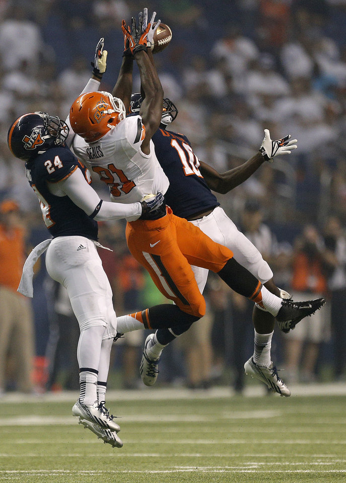 Photo - Oklahoma State's Jhajuan Seales (81) makes a catch as he is double teamed by UTSA's Darrien Starling (24) and Brian King (10) during the second half of a college football game between the University of Texas at San Antonio Roadrunners (UTSA) and the Oklahoma State University Cowboys (OSU) at the Alamodome in San Antonio, Saturday, Sept. 7, 2013.  Photo by Sarah Phipps, The Oklahoman