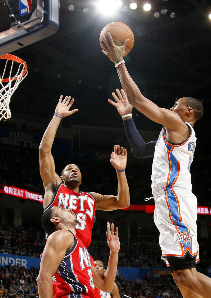 Photo - Oklahoma City's Russell Westbrook shoots the ball over New Jersey's Stephen Graham and Devin Harris, bottom, during the NBA basketball game between the Oklahoma City Thunder and the New Jersey Nets at the Oklahoma City Arena, Wednesday, Dec. 29, 2010.  Photo by Bryan Terry, The Oklahoman