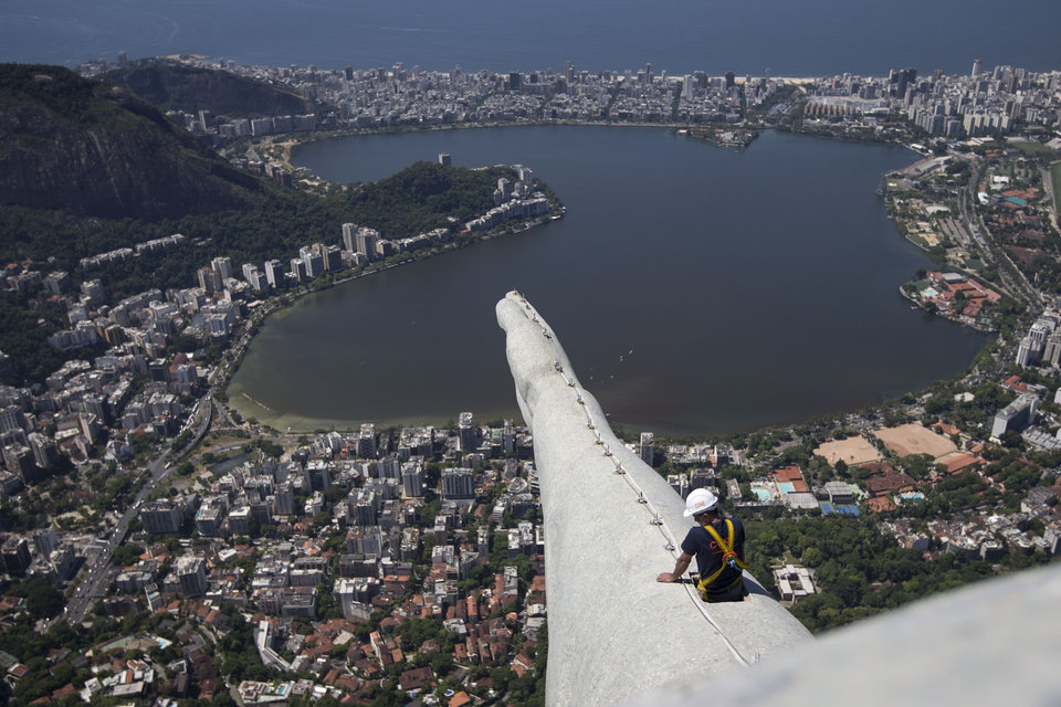 Photo - A worker inspects the arm of the Christ Redeemer statue in Rio de Janeiro, Brazil, Tuesday, Jan. 21, 2014. The famed statue is being examined after two fingers and the head were chipped during recent lightning storms. Officials say they'll place more lightning rods on the statue in an effort to prevent future damage. (AP Photo/Felipe Dana)