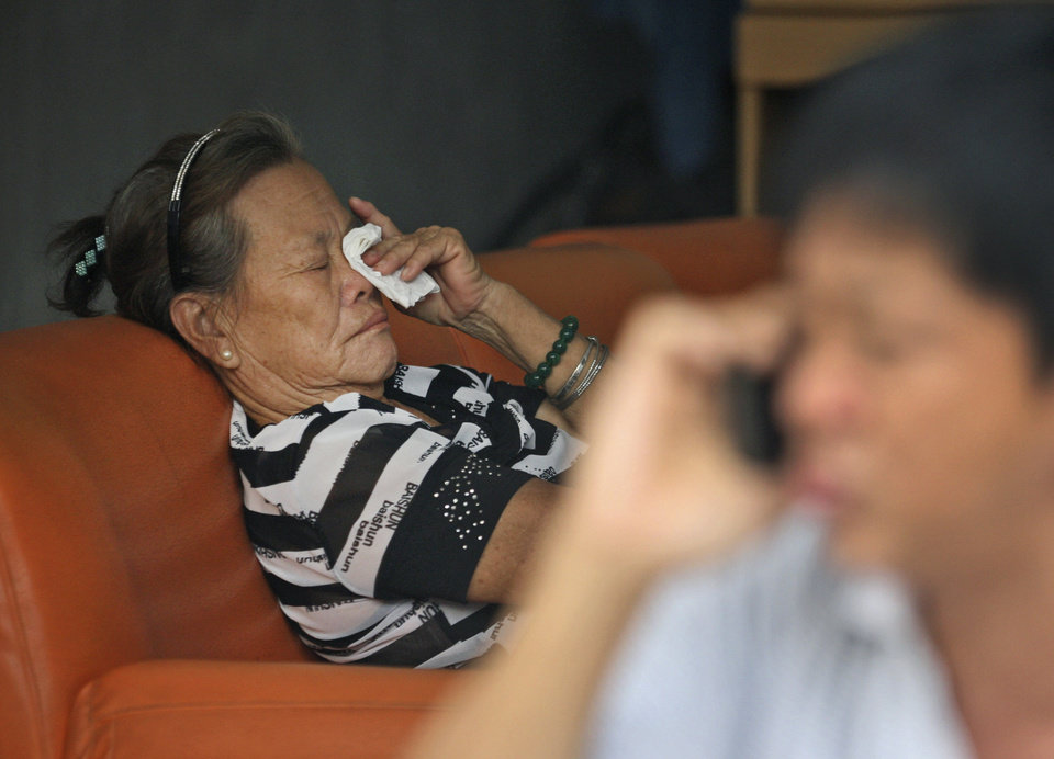 Photo - Suwarni the mother of Sugianto Lo, who was onboard the Malaysia Airlines plane MH370 with his wife Vinny, weeps as an unidentified relative makes a phone call at her residence in Medan, North Sumatra, Indonesia, Tuesday, March 25, 2014. After 17 days of desperation and doubt over the missing Malaysia Airlines jet, the country's officials said an analysis of satellite data points to a