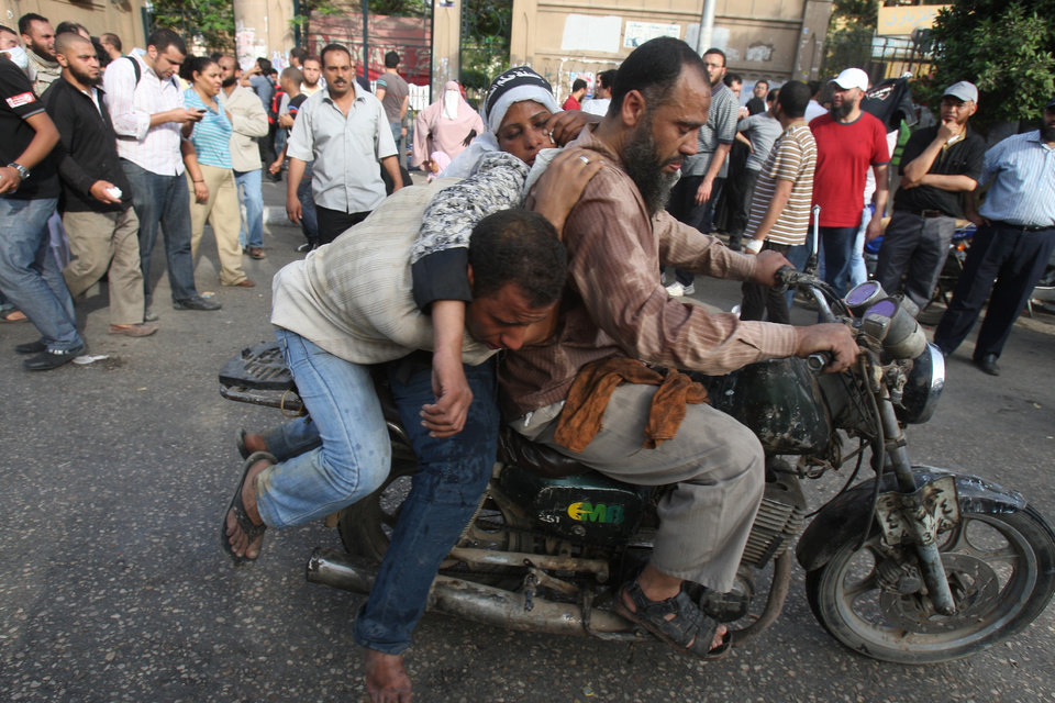 Photo -   Injured protesters are evacuated by motorbike in Cairo, Egypt, Friday, May 4, 2012. Egyptian armed forces and protesters clashed in Cairo on Friday, with troops firing water cannons and tear gas at demonstrators who threw stones as they tried to march on the Defense Ministry, a flashpoint for a new cycle of violence only weeks ahead of presidential elections.(AP Photo/Mohammed Abu Zaid)