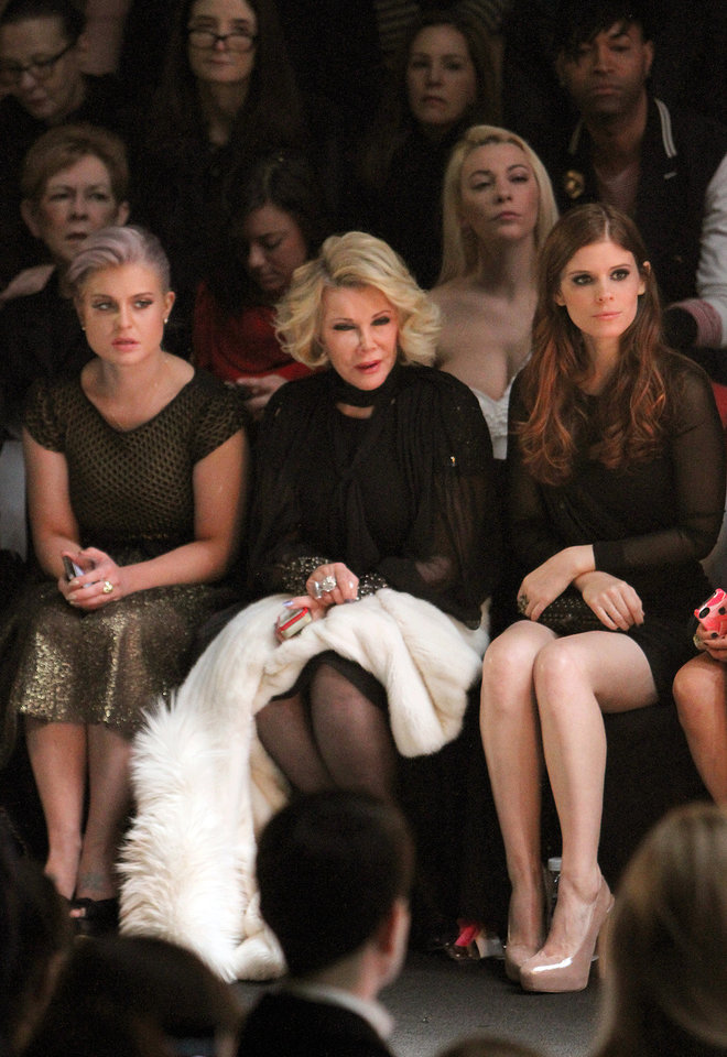 Photo - FILE - In this Feb. 14, 2012 file photo, TV personalities Kelly Osbourne left, Joan Rivers, center, and actress Kate Mara attend the Badgley Mischka Fall 2012 show during Fashion Week in New York. Rivers, the raucous, acid-tongued comedian who crashed the male-dominated realm of late-night talk shows and turned Hollywood red carpets into danger zones for badly dressed celebrities,  died Thursday, Sept. 4, 2014. She was 81. Rivers was hospitalized Aug. 28, after going into cardiac arrest at a doctor's office. (AP Photo/ Donald Traill, File)