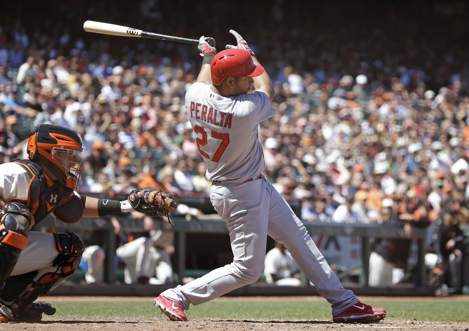Photo - St. Louis Cardinals' Jhonny Peralta (27) singles in the seventh inning of their baseball game against the San Francisco Giants as Giants catcher Buster Posey looks on Thursday, July 3, 2014, in San Francisco. St. Louis won the game 7-2. (AP Photo/Eric Risberg)