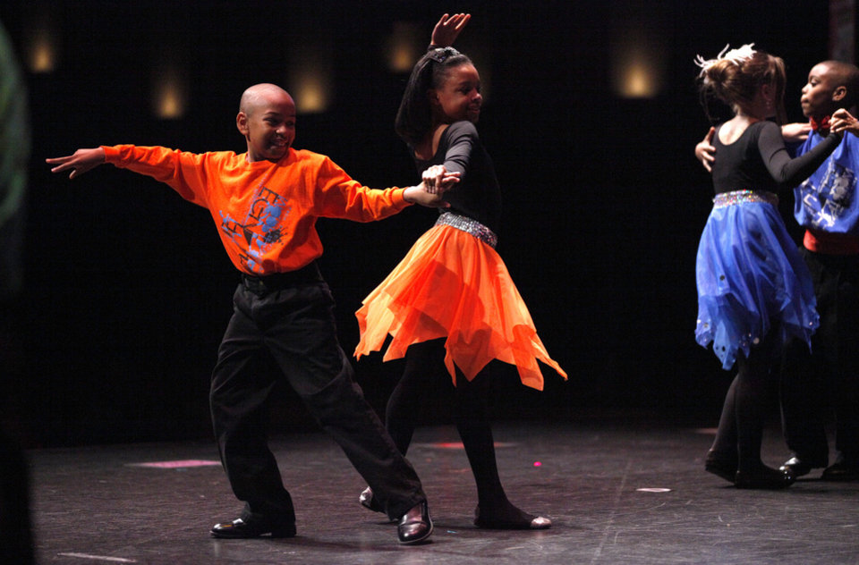 Enrico Jaurdon, 10, and Kyla Wade, 10, from Will Rogers Elementary, perform during a ballroom dance competition at the Rose State Performing Arts Theatre.