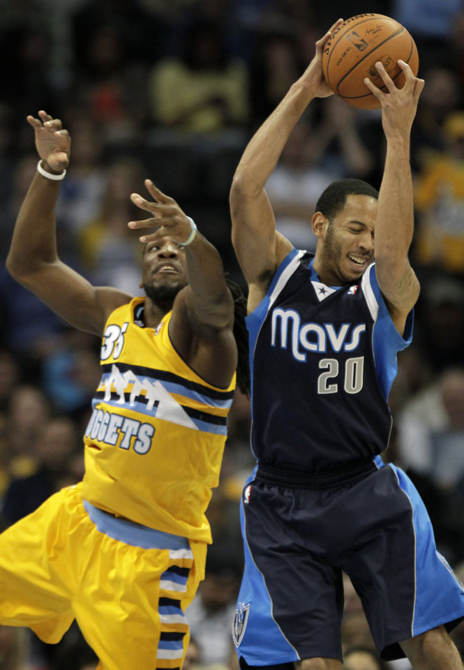 Photo - Denver Nuggets power forward Kenneth Faried (35) swats at the ball controlled by Dallas Mavericks point guard Devin Harris (20) in the first quarter of an NBA game in Denver on Wednesday, March 5, 2014.(AP Photo/Joe Mahoney)