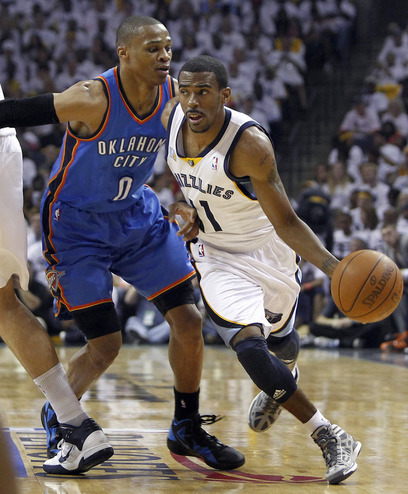 Photo - Memphis Grizzlies guard Mike Conley (11) moves past Oklahoma City Thunder guard Russell Westbrook (0) during the first half of Game 4 of a second-round NBA basketball playoff series on Monday, May 9, 2011, in Memphis, Tenn. (AP Photo/Wade Payne)