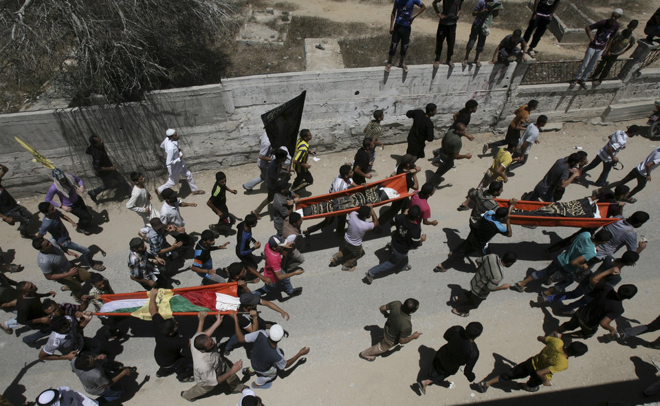 Photo - Mourners carry bodies of Palestinian people killed in an Israeli air strike on a building near their family houses, during their funerals in Rafah refugee camp, southern Gaza Strip, Friday July 11, 2014. Israel launched the Gaza offensive to stop incessant rocket fire that erupted after three Israeli teenagers were kidnapped and killed in the West Bank and a Palestinian teenager was abducted and burned to death in an apparent reprisal attack. The military says it has hit more than 1,100 targets already, mostly what it identified as rocket-launching sites, bombarding the territory on average every five minutes. (AP Photo/Eyad Baba)