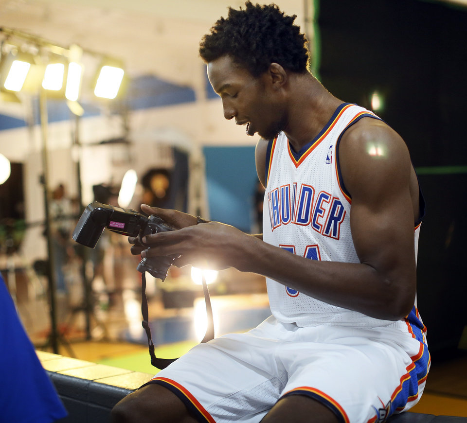 Photo - Hasheem Thabeet checks out a photographer's camera during media day for the Oklahoma City Thunder NBA basketball team at the Thunder Events Center in Oklahoma City, Monday, Oct. 1, 2012.  Photo by Nate Billings, The Oklahoman