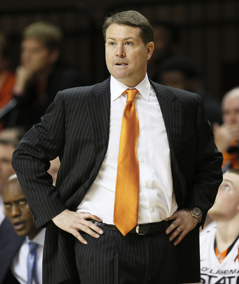 Photo - OSU head coach Travis Ford watches from the bench area during a men's college basketball game between Oklahoma State University and the University of Texas at Gallagher-Iba Arena in Stillwater, Okla., Saturday, March 2, 2013. OSU won, 78-65. Photo by Nate Billings, The Oklahoman