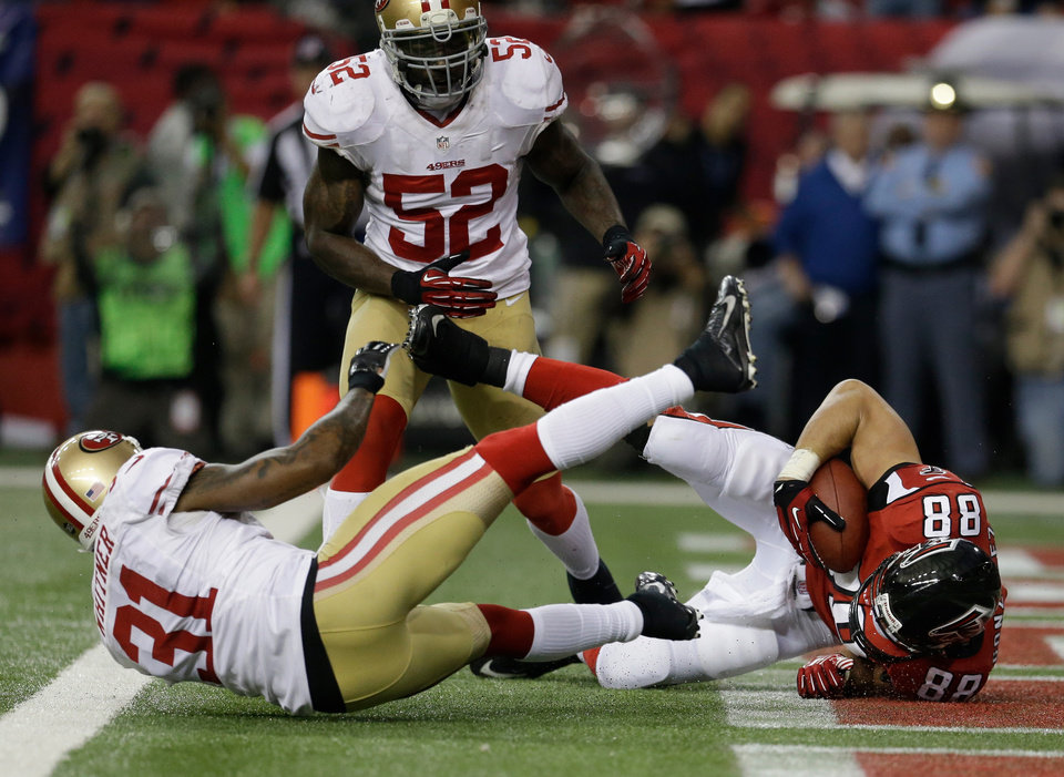 Atlanta Falcons' Tony Gonzalez catches a 10-yard touchdown pass in front of San Francisco 49ers' Donte Whitner (31) during the first half of the NFL football NFC Championship game Sunday, Jan. 20, 2013, in Atlanta. Center is 49ers Patrick Willis. (AP Photo/Mark Humphrey)