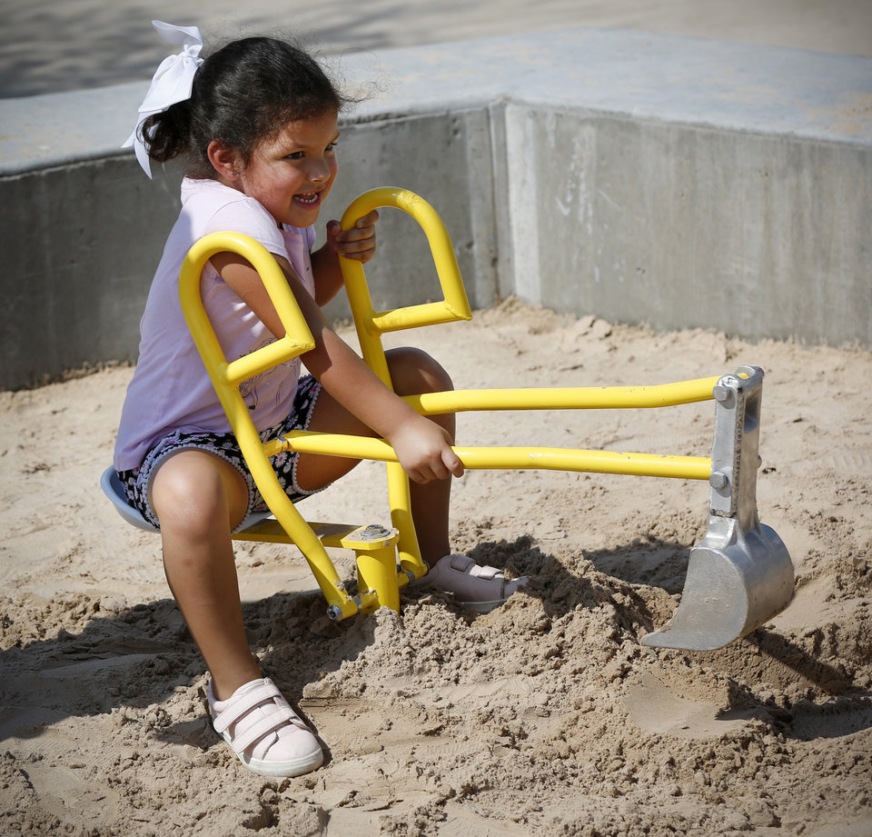 Photo - Ruby Ramirez, 4, plays in the sand in the children's playground during the grand opening weekend of Scissortail Park in Oklahoma City, Saturday, Sept. 28, 2019. [Nate Billings/The Oklahoman]