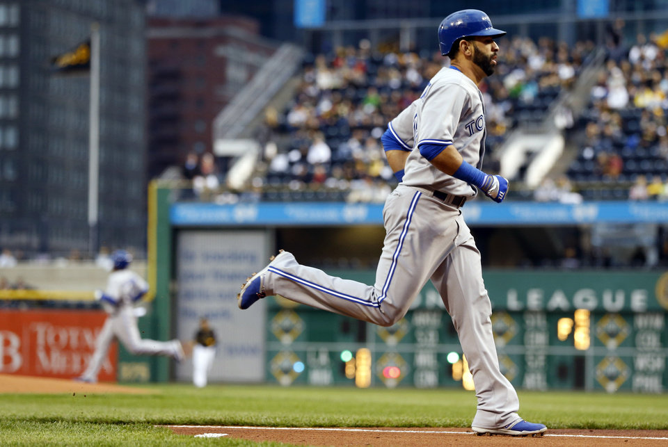 Photo - Toronto Blue Jays' Jose Bautista, right, heads home to score as Edwin Encarnacion, background, goes to second with a double in the first inning of a baseball game against the Pittsburgh Pirates, Friday, May 2, 2014, in Pittsburgh. (AP Photo/Keith Srakocic)