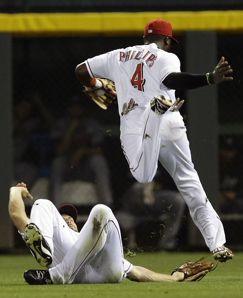 Photo - Cincinnati Reds second baseman Brandon Phillips (4) jumps over right fielder Chris Heisey to avoid a collision after Phillips caught a pop fly by Atlanta Braves' Justin Upton in the fourth inning of a baseball game, Saturday, Aug. 23, 2014, in Cincinnati. (AP Photo/Al Behrman)