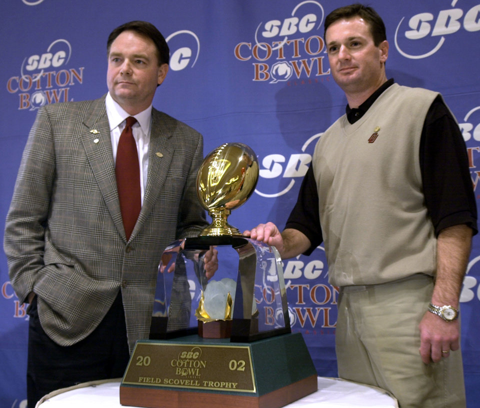 Photo - DALLAS / COLLEGE FOOTBALL / UNIVERSITY OF OKLAHOMA: OU head coach Bob Stoops and Arkansas head coach Houston Nutt pose with the Field Scovell Trophy after answering questions about the Cotton Bowl.  Staff photo by Bryan Terry