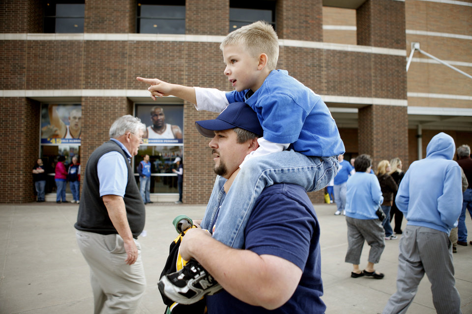 Photo - Ryan Weeres of Okarche carries his son Landon Weeres, 6, outside the Oklahoma CIty Arena before the NBA basketball game between the Denver Nuggets and the Oklahoma City Thunder in the first round of the NBA playoffs at the Oklahoma City Arena, Wednesday, April 27, 2011. Photo by Bryan Terry, The Oklahoman