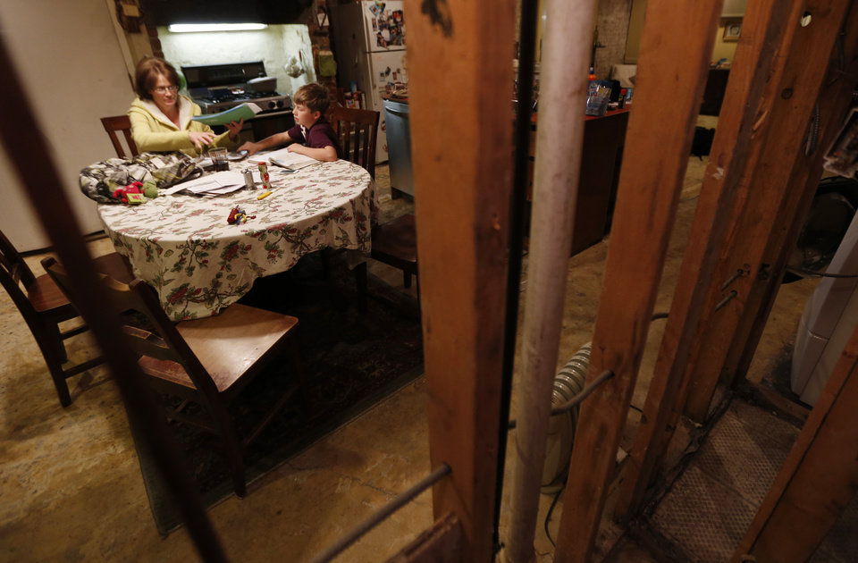 In this Thursday, Jan. 17, 2013 photo, seen through the beams of a gutted wall, Irene Sobolov, left, sits at a table while her 10-year-old son Joey Sobolov works on his fifth grade science homework in their home in Hoboken, N.J. The living and dining rooms of the Sobolov's home, which are below ground in the basement of their home, were damaged in the floods caused by Superstorm Sandy. Many people in Hoboken, Jersey City and Manhattan who live or have businesses in garden-level buildings have had their flood insurance claims denied, because full coverage does not extend to structures that are underground. Home and business owners are now eligible for grant money under the federal Sandy relief bill, but some are calling for the national flood insurance rules to be changed, saying they are unfair to urban areas. (AP Photo/Julio Cortez)