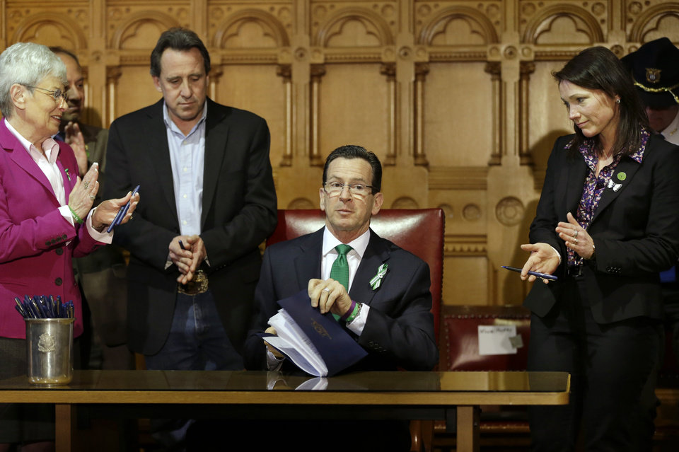 Photo - Connecticut Gov. Dannel P. Malloy, center, completes signing legislation at the Capitol in Hartford, Conn., Thursday, April 4, 2013, that includes new restrictions on weapons and large capacity ammunition magazines, a response to last year's deadly school shooting in Newtown. Neil Heslin, second from left, father of Sandy Hook shooting victim Jesse Lewis, Nicole Hockley, right, mother of Sandy Hook School shooting victim Dylan, and Conn. Lt. Gov. Nancy Wyman, left, applaud. The legislation adds more than 100 firearms to the state's assault weapons ban, sets eligibility rules for buying ammunition, and creates what officials have called the nation's first dangerous weapon offender registry. (AP Photo/Steven Senne)
