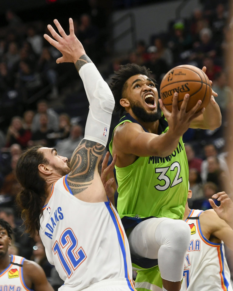 Photo - Minnesota Timberwolves center Karl-Anthony Towns (32) goes up to shoot past Oklahoma City Thunder center Steven Adams (12) during the first half of an NBA basketball game Saturday, Jan. 25, 2020, in Minneapolis. (AP Photo/Craig Lassig)
