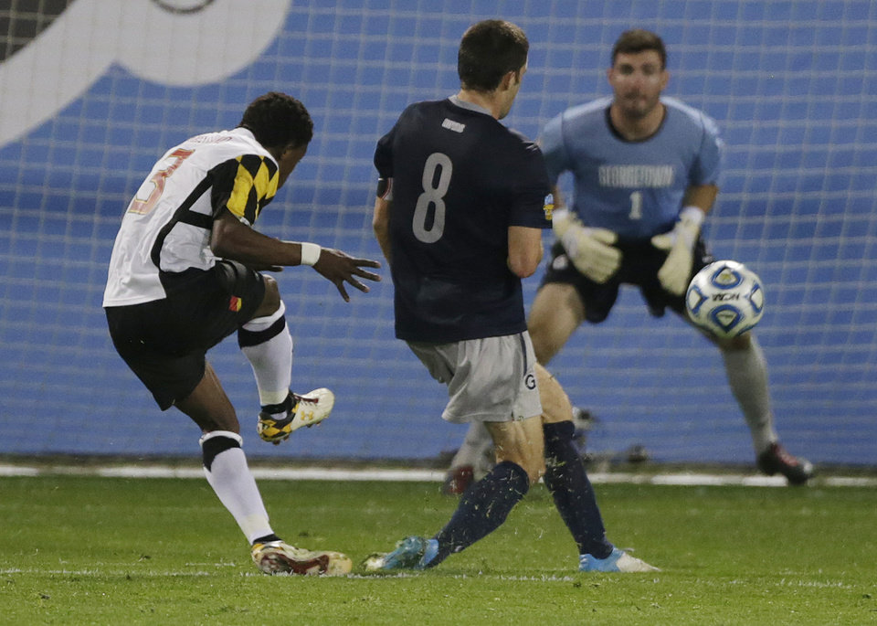 Maryland's Christiano Francois scores a goal as Georgetown's Tomas Gomez (1) and  Tommy Muller (8) defend in the second half of a NCAA College Cup men's championship semifinal soccer match at Regions Park, Friday, Dec. 7, 2012, in Hoover, Ala. (AP Photo/Dave Martin)