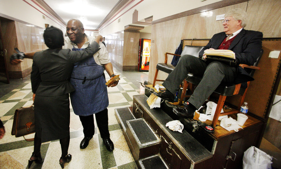 Cleo Fields, center, with Cleo's Professional Shine, stops to get a hug while shining the shoes of attorney John Foley, of Okla. City, at his shoeshine booth on the ground floor of the Oklahoma County Courthouse in Oklahoma City Friday, March 23, 2012. Photo by Paul B. Southerland, The Oklahoman