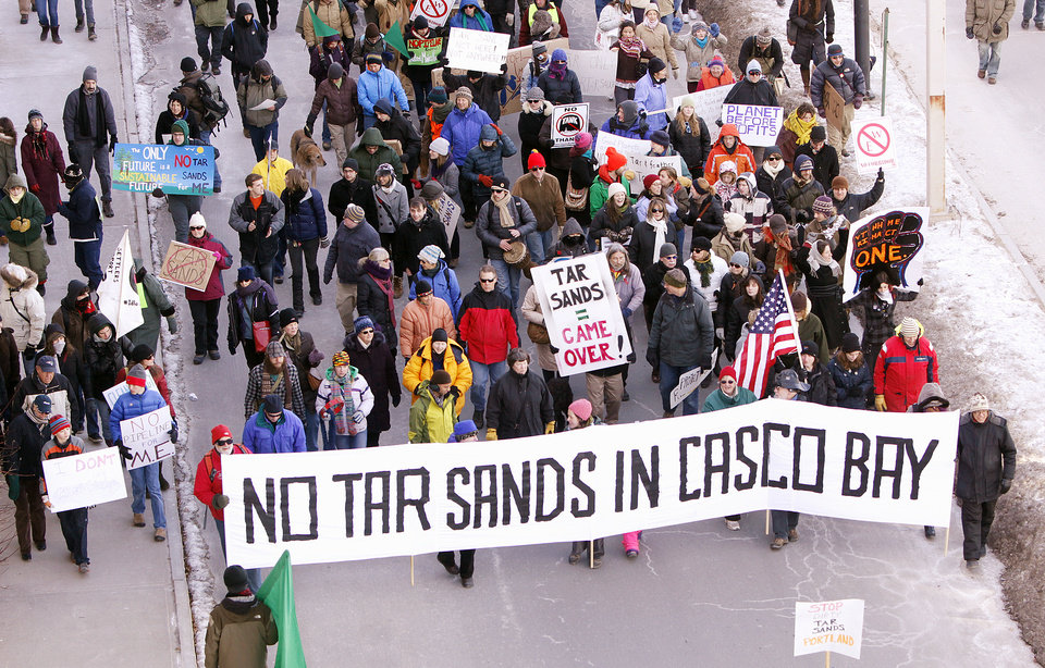 Protesters march onto the Maine State Pier in Portland on Saturday, Jan.  26, 2013 to attend a rally against the possibility of tar sands oil being piped from Canada across northern New England to Portland, Maine. Critics of so-called tar sands oil say Canadian energy firm Enbridge Inc. is eyeing an existing oil pipeline that carries oil from Portland to Montreal with the idea of reversing the flow and sending the oil across Vermont, New Hampshire and Maine to Portland. (AP Photo/Portland Press Herald, Gregory Rec)