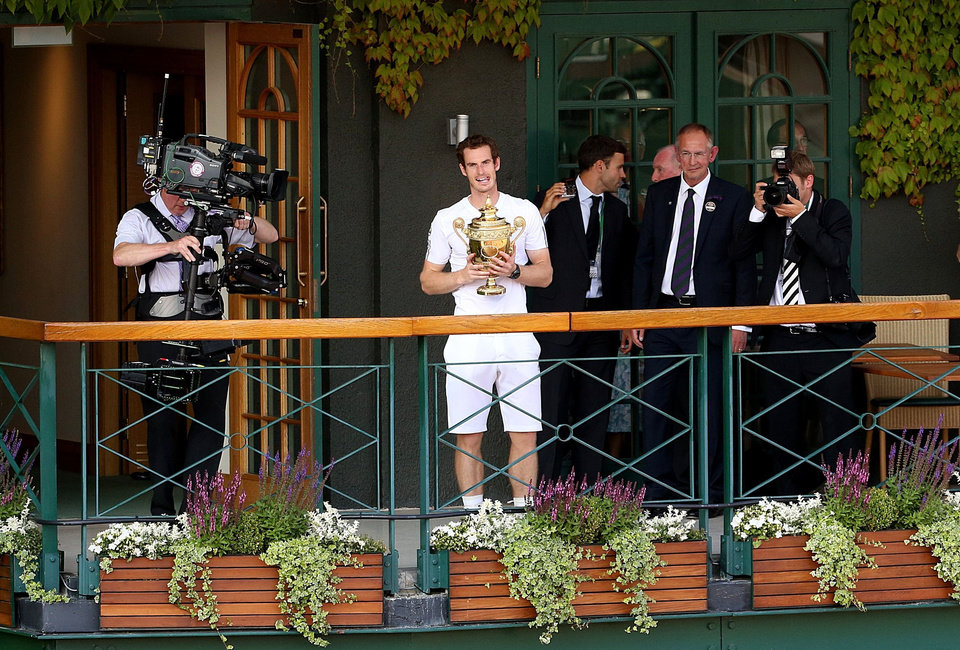 Photo - Britain's Andy Murray stands on the balcony of Centre Court with the tropjy after winning the Men's singles title on during day thirteen of the Wimbledon Championships at The All England Lawn Tennis and Croquet Club, Wimbledon, London, Sunday July 7, 2013. (AP Photo/Dominic Lipinski, PA) UNITED KINGDOM OUT