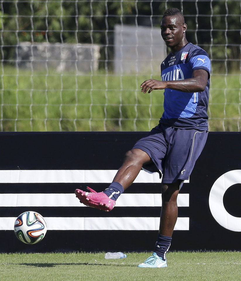 Photo - Italy's Mario Balotelli kicks the ball during a training session in Mangaratiba, Brazil, Tuesday, June 17, 2014. Italy plays in group D at the 2014 soccer World Cup. (AP Photo/Antonio Calanni)