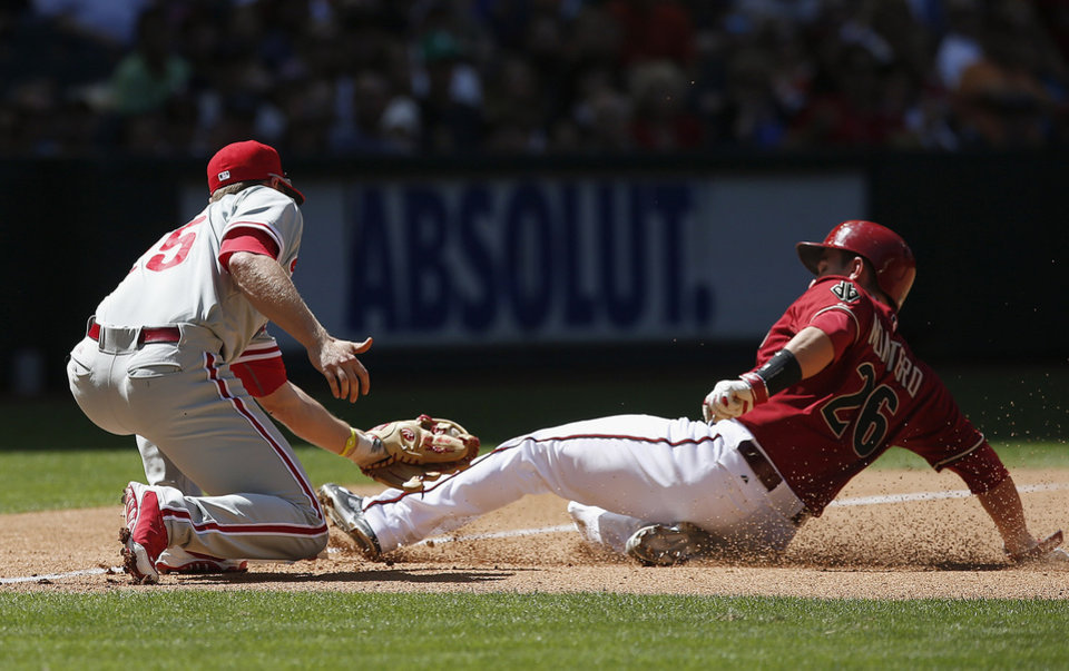 Photo - Arizona Diamondbacks' Miguel Montero (26) slides safely into third base as Philadelphia Phillies' Cody Asche, left, applies a late tag during the fourth inning of a baseball game on Sunday, April 27, 2014, in Phoenix. (AP Photo/Ross D. Franklin)
