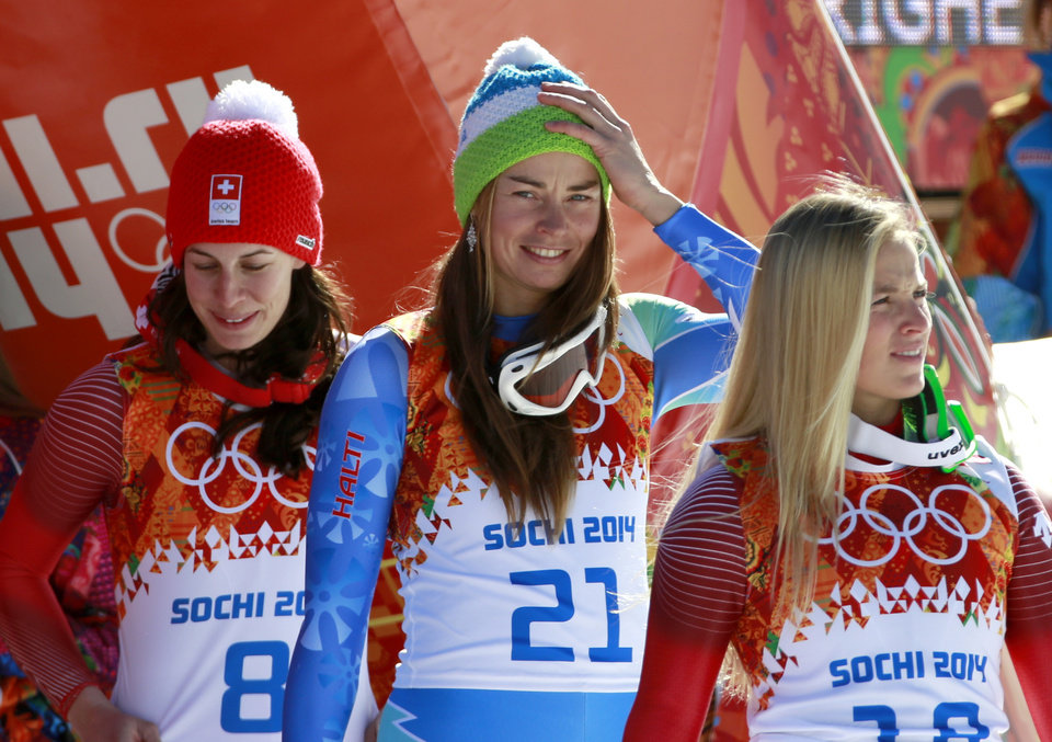 Photo - Women's downhill gold medalists Switzerland's Dominique Gisin, left, and Slovenia's Tina Maze, center, stand with bronze medalist Switzerland's Lara Gut before a flower ceremony at the Sochi 2014 Winter Olympics, Wednesday, Feb. 12, 2014, in Krasnaya Polyana, Russia. (AP Photo/Gero Breloer)