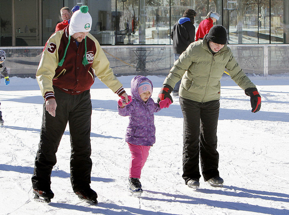 Members of the Wise family — Scott, Arzela, 4, and Nina — skate Saturday at Devon Ice Rink at Myriad Botanical Gardens in  Oklahoma City. Read more about the rink on Page 4A. Photo by Paul Hellstern, The Oklahoman