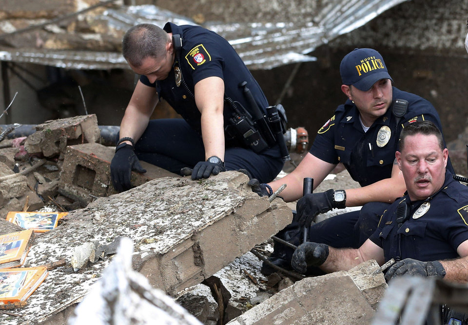 Moore police dig through the rubble of the Plaza Towers Elementary School following a tornado in Moore, Okla., Monday, May 20, 2013. A tornado as much as a mile (1.6 kilometers) wide with winds up to 200 mph (320 kph) roared through the Oklahoma City suburbs Monday, flattening entire neighborhoods, setting buildings on fire and landing a direct blow on an elementary school. (AP Photo/Sue Ogrocki) ORG XMIT: OKSO120