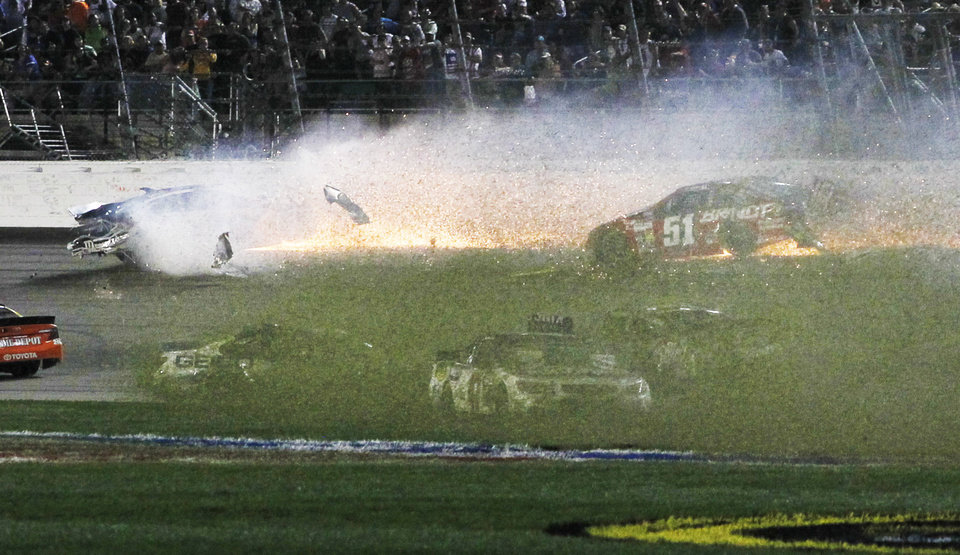 Photo - Drivers spin into the infield as David Gilliland, top left, and Justin Allgaier (51) tangle with the wall during a NASCAR Sprint Cup Series auto race at Kansas Speedway in Kansas City, Kan., Saturday, May 10, 2014. (AP Photo/Colin E. Braley)