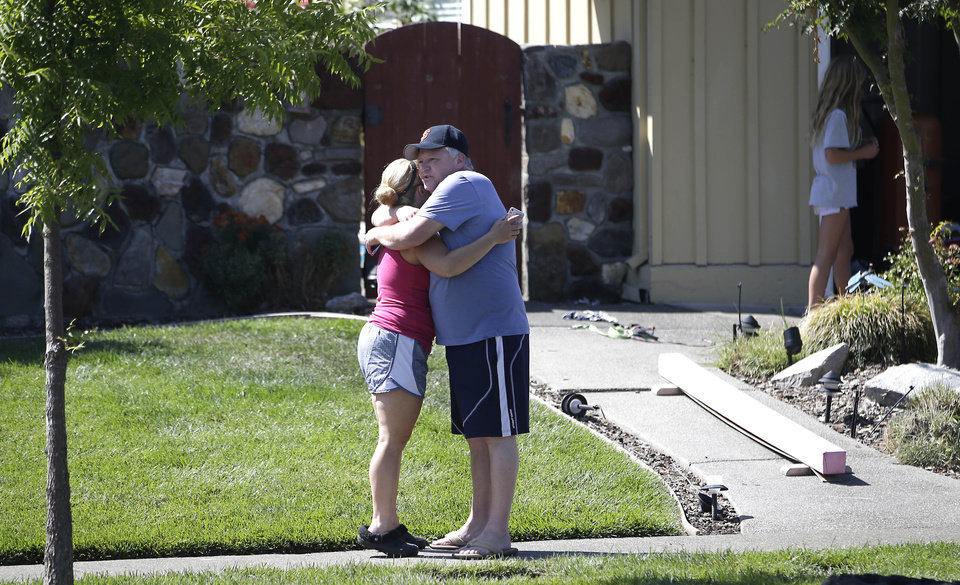 Photo - Neighbors Kelli Harpe and Toby Rompel greet each other with a hug outside their homes that were damaged by an early morning earthquake Sunday, Aug. 24, 2014, in Napa, Calif.  The largest earthquake to hit the San Francisco Bay Area in 25 years struck before dawn on Sunday.  (AP Photo/Rich Pedroncelli)