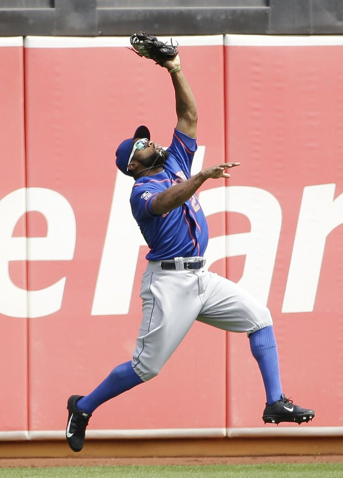 Photo - New York Mets left fielder Eric Young Jr. catches a fly ball hit by the Oakland Athletics' Stephen Vogt in the first inning of their interleague baseball game Wednesday, Aug. 20, 2014, in Oakland, Calif. (AP Photo/Eric Risberg)