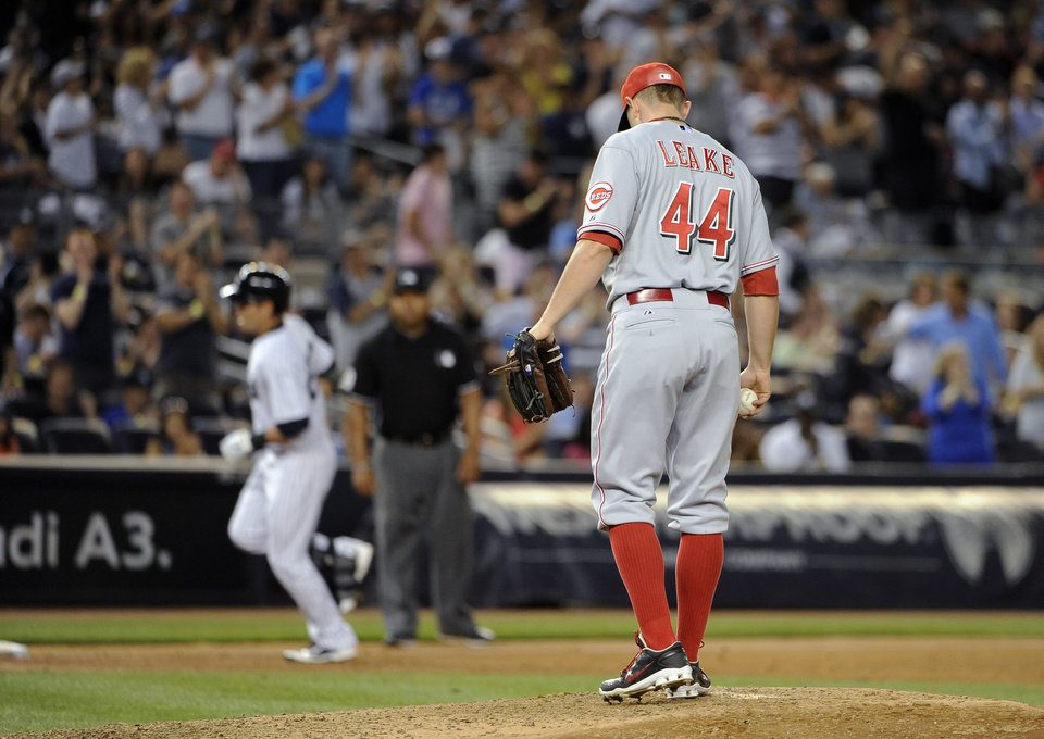 Photo - Cincinnati Reds starting pitcher Mike Leake stands on the mound as New York Yankees' Jacoby Ellsbury rounds third base after hitting a two-run home run in the fifth inning of an interleague baseball game at Yankee Stadium on Friday, July 18, 2014, in New York. (AP Photo/Kathy Kmonicek)