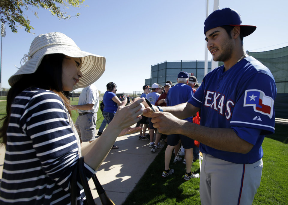 Photo - Texas Rangers pitcher Martin Perez, right, returns an autographed ball to Yumiko Seki, left, of Tokyo, after a pitchers and catchers workout during spring training baseball practice, Monday, Feb. 17, 2014, in Surprise, Ariz. (AP Photo/Tony Gutierrez)