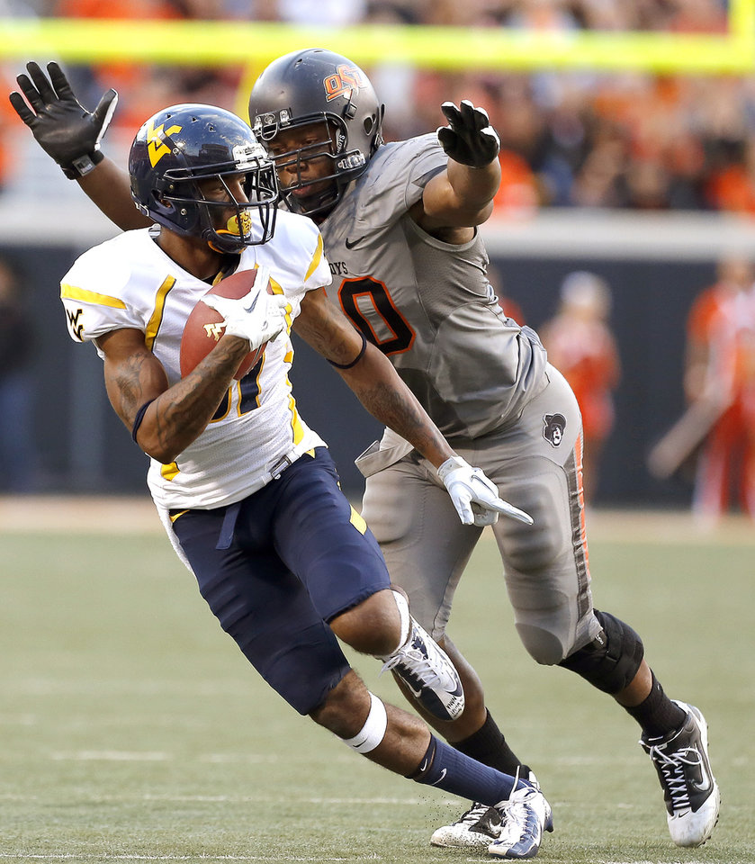 Photo - Oklahoma State's Tyler Johnson (40) tackled West Virginia's J.D. Woods (81) during a college football game between Oklahoma State University (OSU) and the West Virginia University at Boone Pickens Stadium in Stillwater, Okla., Saturday, Nov. 10, 2012. Photo by Sarah Phipps, The Oklahoman