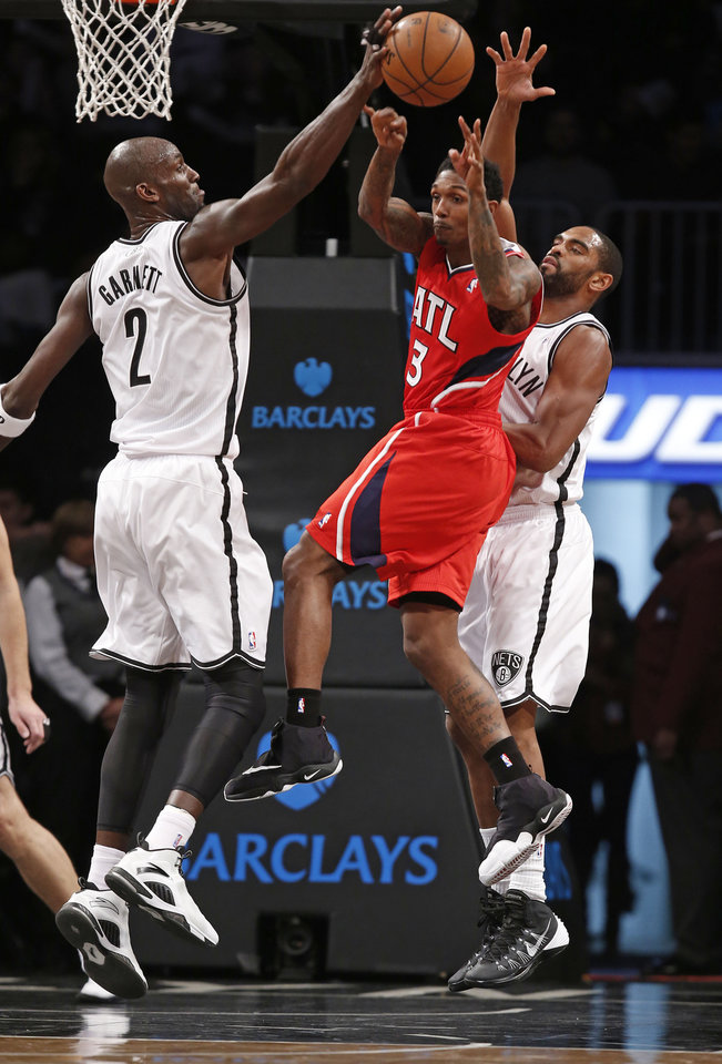 Photo - Atlanta Hawks guard Louis Williams (3) passes but Brooklyn Nets forward Kevin Garnett (2) blocks the pass with Nets guard Alan Anderson (6) defending in the first half of their NBA basketball game at the Barclays Center, Monday, Jan. 6, 2014, in New York. (AP Photo/Kathy Willens)