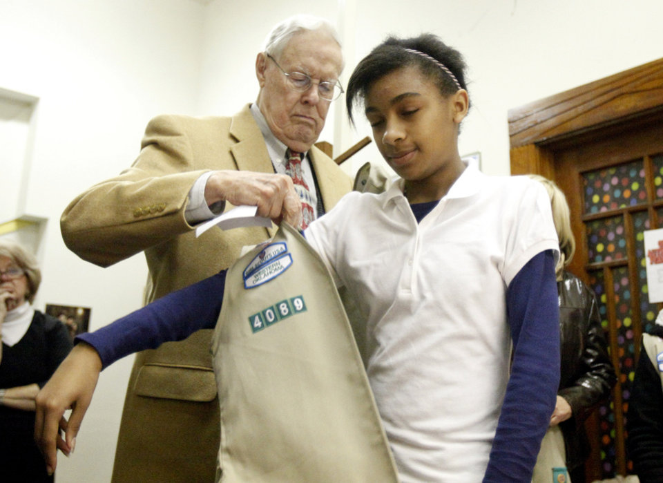 George Camp puts a vest on Mallory West during the Girl Scout Troop 4089 Investiture Ceremony, Friday, Jan.  21, 2011, at Taft Middle School in Oklahoma City. Photo by Sarah Phipps, The Oklahoman
