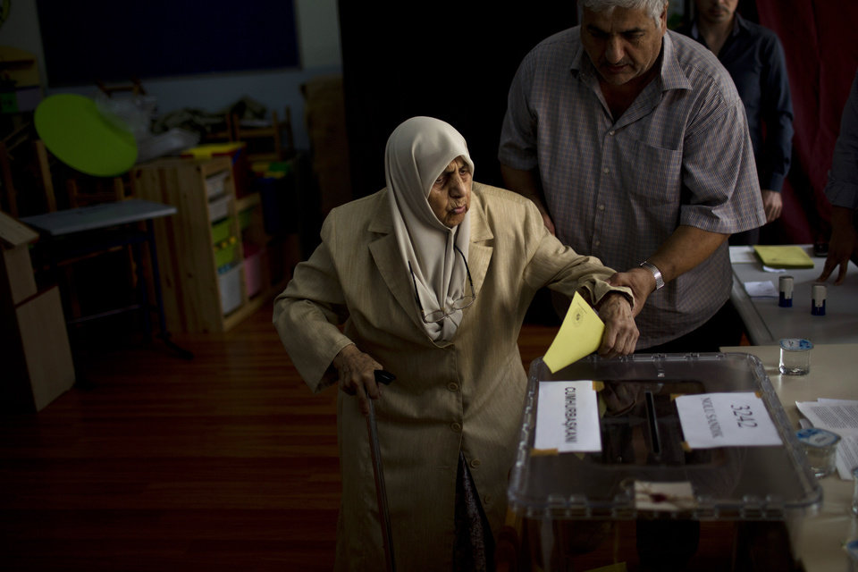 Photo - A woman is assisted as she casts her vote for the Turkey's presidential election at a polling station in Istanbul, Turkey, on Sunday, Aug. 10, 2014. Turks were voting in their first direct presidential election Sunday, a watershed event in the 91-year history of a country where the president was previously elected by Parliament. Prime Minister Recep Tayyip Erdogan, who has dominated Turkey's politics for the past decade, is the strong front-runner to replace the incumbent, Abdullah Gul, for a five-year term. (AP Photo/Emilio Morenatti)