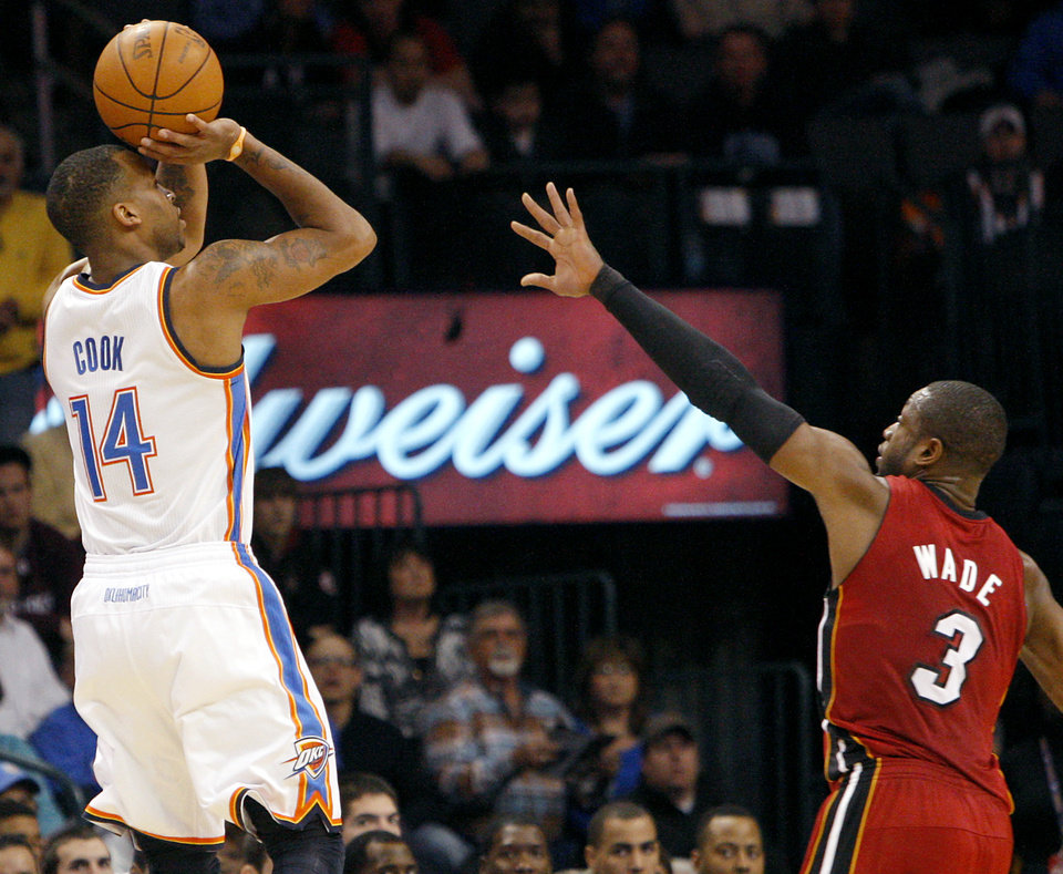 Photo - Oklahoma City's Daequan Cook puts a shot over Miami's Dwyane WadeWade during their NBA basketball game at the OKC Arena in Oklahoma City on Thursday, Jan. 30, 2011. Photo by John Clanton, The Oklahoman