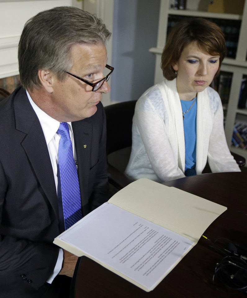 Photo - Tanya Fowle, right, wife of Jeffrey Fowle, listens as attorney Tim Tepe reads a statement from the family, Monday, June 9, 2014, in Lebanon, Ohio. Tepe said that Jeffrey Fowle was on vacation as part of a tour when he was detained in North Korea last week. (AP Photo/Al Behrman)