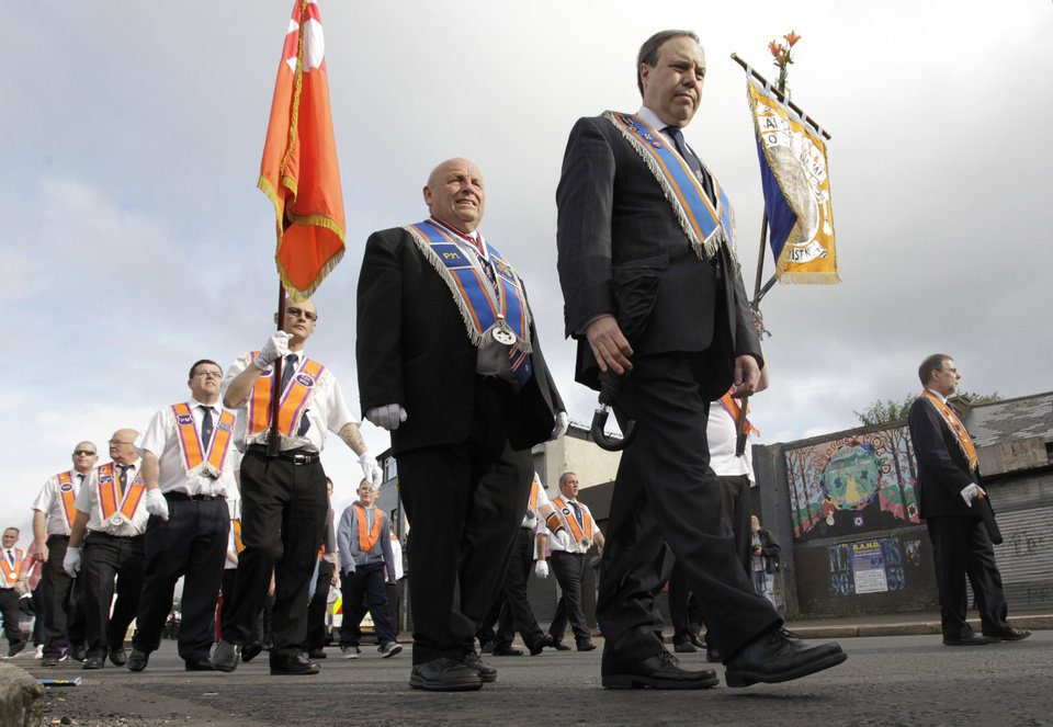Photo -   Orange Order members march past the mainly Catholic Ardyone area of North Belfast, Northen Ireland, Thursday, July 12, 2012. The Twelfth of July is the busiest day of the marching season in Northern Ireland with thousands of Orangemen and women, accompanied by marching bands, taking part in hundreds of parades. The Orange Order holds its main Belfast event, which commemorates King William III's 1690 Battle of the Boyne victory over Catholic King James II. (AP Photo/Peter Morrison)