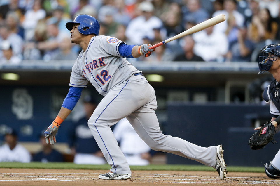 Photo - New York Mets' Juan Lagares watches his two-run single against the San Diego Padres during the first inning in a baseball game  Friday, July 18, 2014, in San Diego. (AP Photo/Gregory Bull)